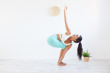 healthy lifestyle beautiful positive woman brunette yoga instructor doing exercise on white wall background. Copyspace