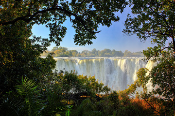 Victoria Falls, waterfall in southern Africa on the Zambezi River at the border between Zambia and Zimbabwe. Landscape in Africa. A lot of water durring summer season