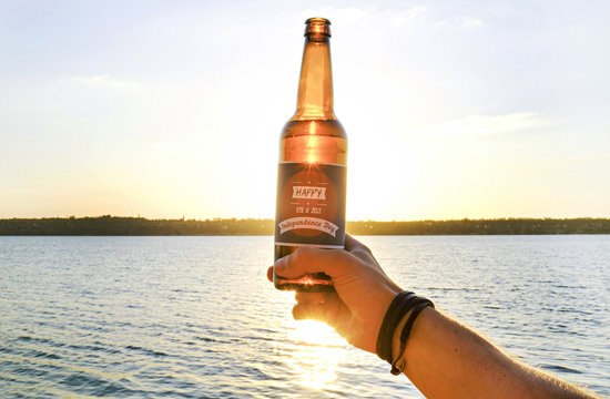 4th of July celebration party. Young man holding brown beer bottle with Happy Independence day label. Male having a holiday drink by the river in sunset light. Festive background, close up, copy space