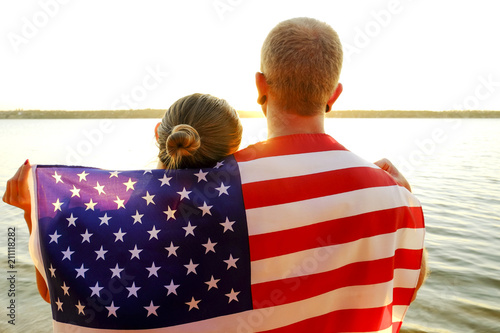 Rear view of young American patriotic couple hugging with USA flag on their backs enjoying beautiful summer sunset by the river. Independence day celebration concept. Background, close up, copy space.