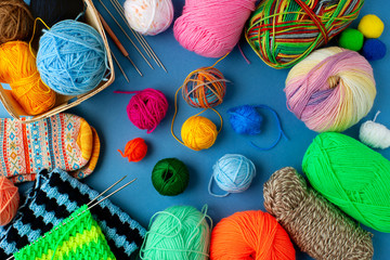 Yarn and knitting needles on a blue background. A lot of colorful yarn is folded into a frame on a blue background. Knitting as a kind of needlework.