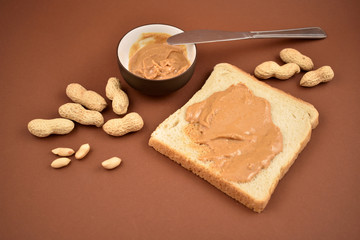 Peanut Butter stock images. Bowl of peanut butter on brown background. Toast with peanut butter. Breakfast still life. American delicacy