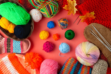 Yarn and knitted clothing on a pink background. Orange knitted cap with bubo, colorful yarn, socks, knitting needles are stacked on a pink background. View from above.
