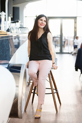 Portrait of a charming young brunette woman with bright make up sitting at a bar in a stylish luxury restaurant on a background of blurred people. Vertical shot