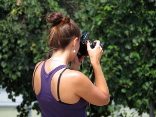 Young woman with a SLR camera in her hands, rear view. Girl photographing on background of summer trees in sunny day
