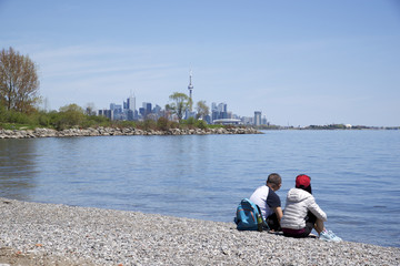 couple day out on the beach with Toronto city scape as background