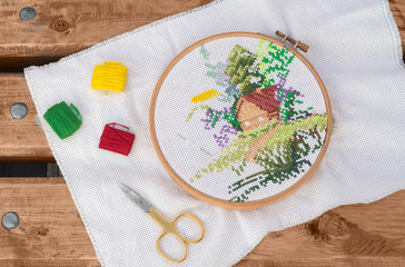 The embroidery is in outdoors. The picture of house is embroidered cross-stitch and accessories for needlework (a needle, the color threads and the scissors) are lying on a wooden bench in a park.