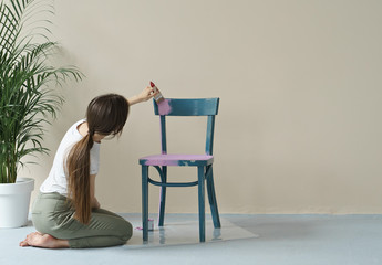 young woman painting chair in pink at home