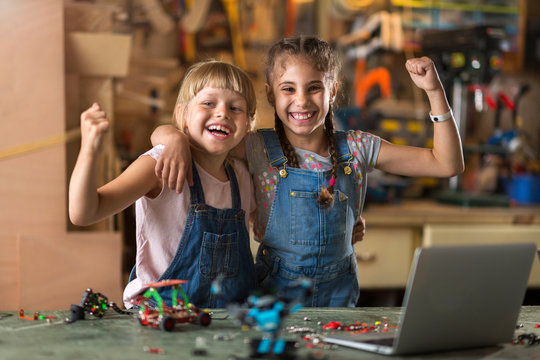 Small girls building toy construction machine