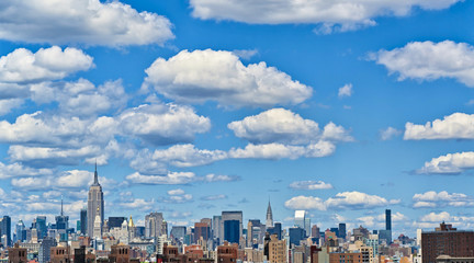 View of the Manhattan skyline (New York City) in daylight with beautiful low clouds in the clear sky. Skyscapers and buildings in the finance district of an American city