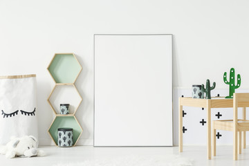 Wooden shelves with cactus boxes and decor on small table standing in white kid room interior with mockup poster on the floor. Paste your photo here