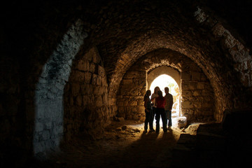 KERAK, JORDAN - Nov 2009: A small group of tourists stand in a dark chamber, silhouetted by glowing sunlight through an archway window inside the ancient crusader castle at Karak near Amman in Jordan