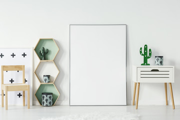 Small cupboard with cactus shaped lamp and decorative box standing in white baby room interior with empty poster with place for your graphic, wooden chair and geometric shelves