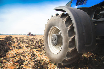 A wheel from a tractor working in the field close up. The concept of agriculture.