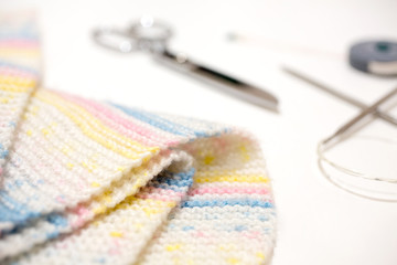 Handmade wool with knitting equipment. Scissors and measuring tape. Frame of knitting needles and scarf on white background. asian.
