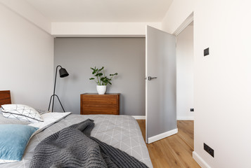Grey blanket on bed in minimal bedroom interior with plant on wooden cabinet near door. Real photo