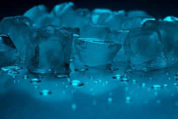A pile of ice cubes in turquoise color and drops of water on a reflecting table