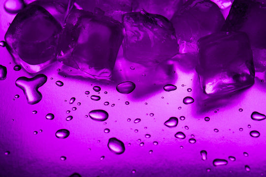A pile of ice cubes in purple on a reflecting table