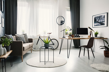 Bright living room interior with sofa with cushions, bike under the window with curtains and hairpin desk with lamp and computer for remote work