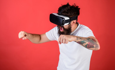 Hipster on excited face driving bike on high speed in virtual reality with modern digital gadget. Virtual driving lessons concept. Man with beard in VR glasses driving motorbike, red background