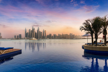 Blick auf Dubai Marina bei Sonnenuntergang mit einem Swimming Pool im Vordergrund