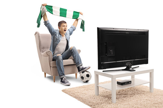 Overjoyed teenage soccer fan holding a scarf and watching a match on television