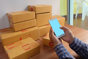 man are holding mobile phone and Product Box, On wooden floor, Online shopping, work at home, e commerce
