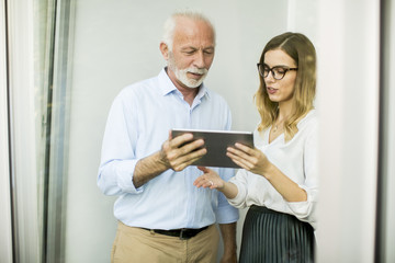 Senior man presenting data to young woman on digital tablet