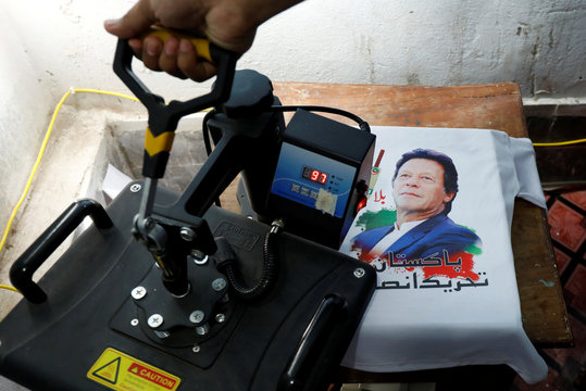 A worker prints a T-shirt, with heat press machine, to be used for a campaign of a political party, at a workshop ahead of general elections in Peshawar