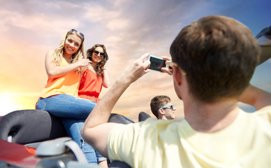 leisure, road trip, travel and people concept - happy friends taking picture by smartphone in convertible car over sky background