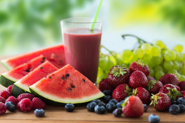 healthy eating, food, dieting and vegetarian concept - glass with fruit and berry juice or smoothie on wooden table over green natural background
