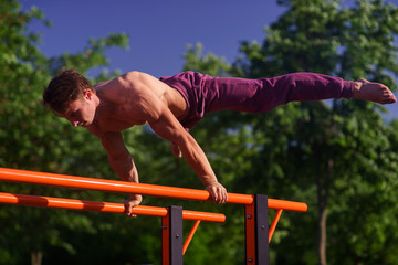 Muscular man making planche on the street. Street workout