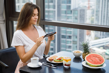 Young and happy woman taking picture of her delicious breakfast