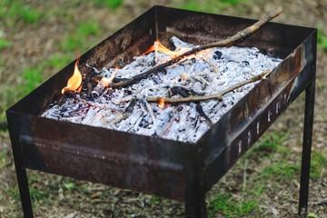 Real portable BBQ grill on background of a fresh green summer landscape. Veritable outdoor grill with wood ashes and fire flames. Public outdoor charcoal grill in park ready for grilling.