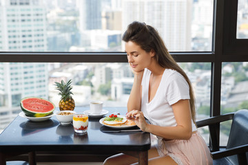 Young woman eating breakfast at morning