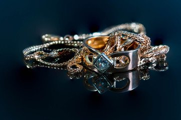 Glowing real gold jewelry with real diamonds on shiny surface  close up macro shot.