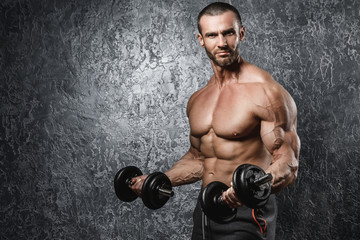 Muscular bodybuilder working out with a dumbbells