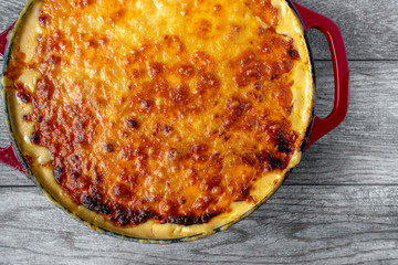 top view baked golden cheese dish in red pan on rustic table