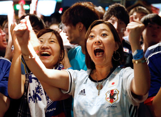 Japanese fans react as they watch a broadcast of the World Cup Group H soccer match Japan vs Poland, at a sports bar in Tokyo