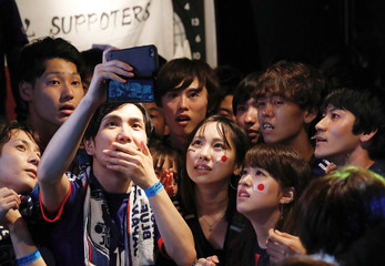 Japanese fans watch a broadcast of the World Cup Group H soccer match Senegal and Columbia through a smartphone after watching a broadcast of the World Cup Group H soccer match Japan vs Poland, at a sports bar in Tokyo