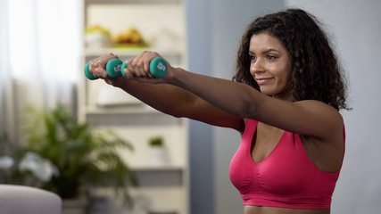 Attractive woman lifting dumbbells, active lifestyle, physical exercise, fitness