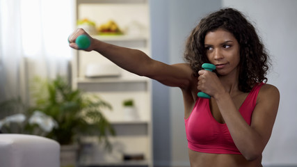 Sporty girl doing boxing movements with dumbbells in hands, fitness workout