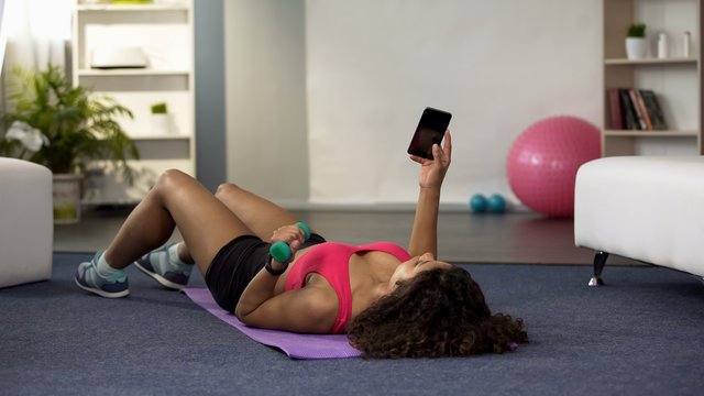 Young woman lifting dumbbell with one hand, holding phone in another, fitness