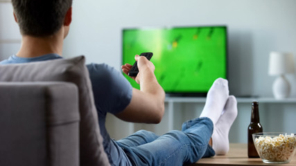Sport fan watching recording of missed soccer match, modern smart tv technology