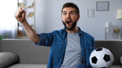 Cheerful guy loudly screaming watching football match, successful game result
