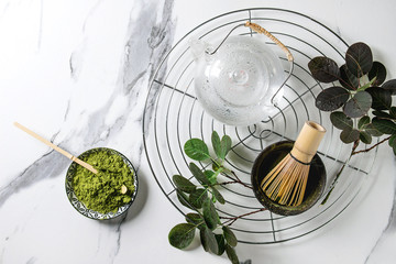 Ingredients for making matcha drink. Green tea matcha powder in ceramic bowl, traditional bamboo spoon, whisk on cooling rack, glass teapot, green branches over white marble background. Flat lay
