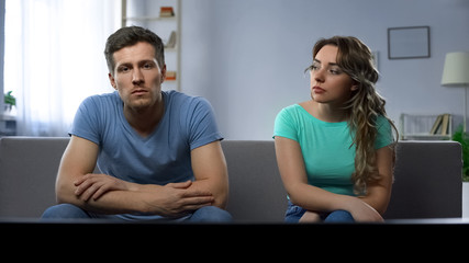 Conflict in family, couple watching tv ignoring each other, misunderstanding