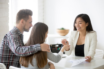 Smiling Asian broker giving keys to millennial couple, buying first home together, female real estate agent presenting keys to young spouses deciding to purchase property. New beginning concept