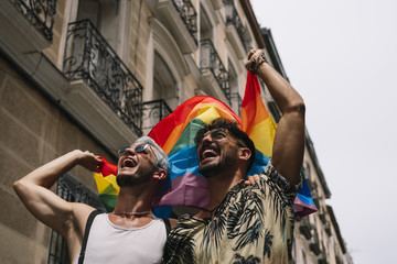 Couple boys with gay pride flag on the street of Madrid city