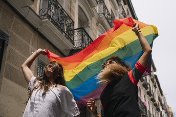 Couple lesbian woman with gay pride flag on the street of Madrid city